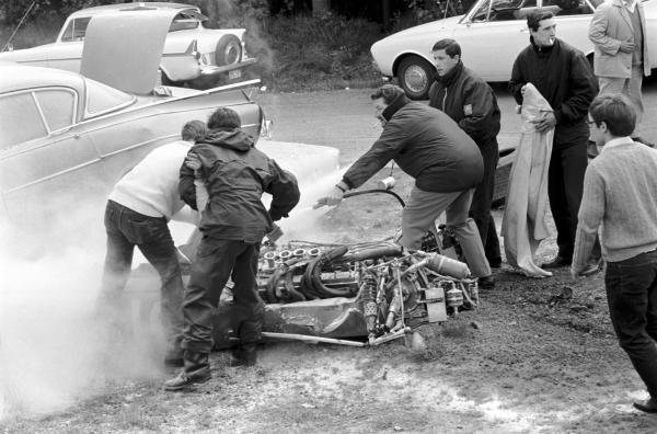 A cigarette wielding fire marshal douses the Cooper T86B of Brian Redman (GBR) following a high speed accident that saw him hitting parked cars on a public road.   Belgian Grand Prix, Spa-Francorchamps, June 9 1968.