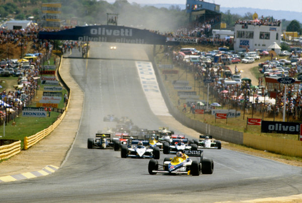 Kyalami, South Africa 17-19 October 1985. Nigel Mansell, Williams FW10 Honda, leads Nelson Piquet and Marc Surer (both Brabham BT54 BMW) at the start. Ref: 85SA07. World Copyright - LAT Photographic
