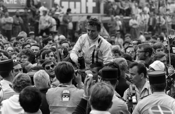Jackie Oliver is held aloft by his team after winning the race.