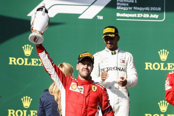 Sebastian Vettel, Ferrari celebrates on the podium with trophy.