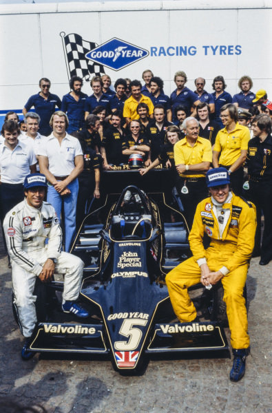 Lotus team photo with Mario Andretti and Ronnie Peterson sitting on a Lotus 79 Ford. Colin Chapman and Nigel Bennett are also visible.