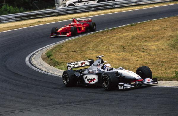 David Coulthard, McLaren MP4-13 Mercedes, leads Michael Schumacher, Ferrari F300.