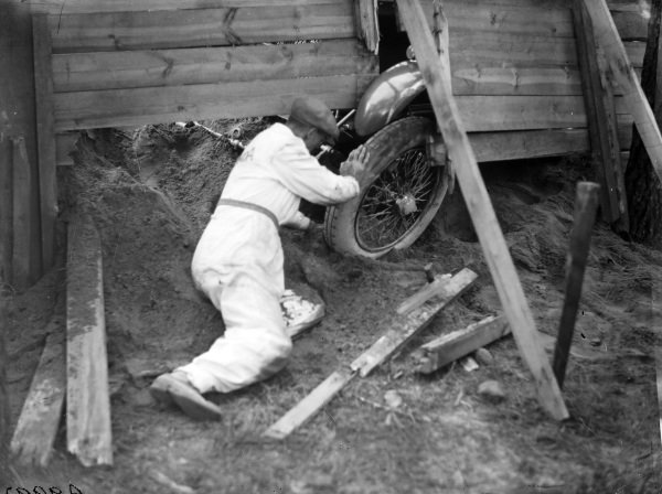 Francis Samuelson tries to dig his front wheel out of the sand after he crashed the F. E. Metcalfe, Lagonda OH 2L Speed, into a sand bank and through a fence.