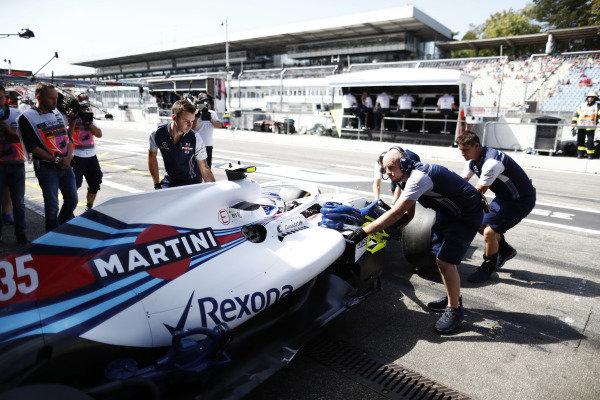 Mechanics push the Sergey Sirotkin Williams FW41 Mercedes into the garage.