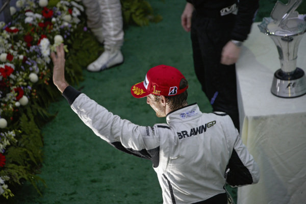 Winner Jenson Button waves to the crowd on the podium.