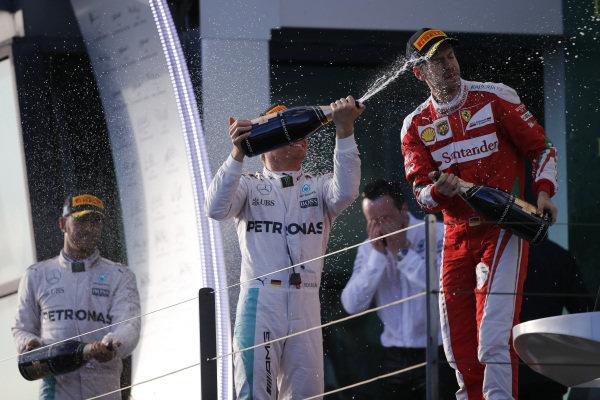 Race winner Nico Rosberg (GER) Mercedes AMG F1, Lewis Hamilton (GBR) Mercedes AMG F1 and Sebastian Vettel (GER) Ferrari celebrate with champagne on the podium at Formula One World Championship, Rd1, Australian Grand Prix, Race, Albert Park, Melbourne, Australia, Sunday 20 March 2016.