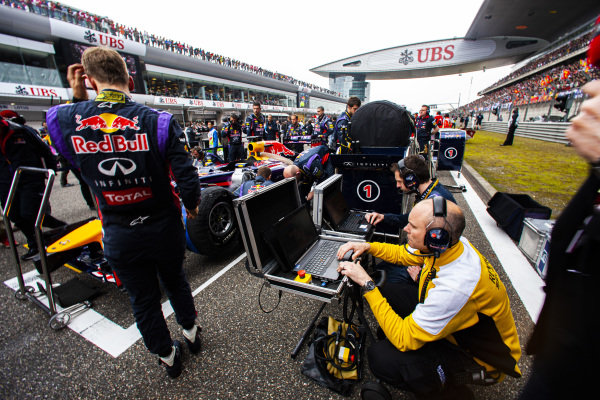 Renault and Red Bull engineers at work beside Sebastian Vettel, who is beside Red Bull RB10 Renault.
