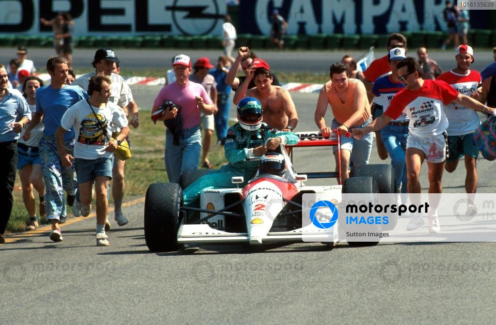 Gerhard Berger (AUT) McLaren MP4/6 finished fourth but ran out of fuel on the slow-down lap just as he was giving Ivan Capelli (ITA) Ð retired -  (seated) a lift back to the pits. Helpful German supporters attempt to push them around the stadium section.  German Grand Prix, Hockenheim, 28 July 1991.