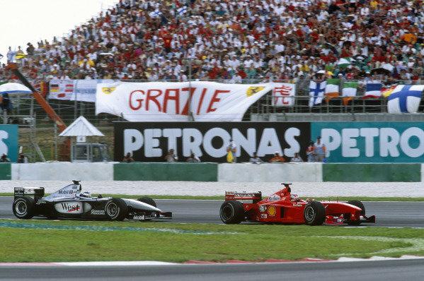 Sepang, Kuala Lumpur, Malaysia. 15-17 October 1999. Michael Schumacher (Ferrari F399) holds up Mika Hakkinen (McLaren MP4/14 Mercedes) alowing team mate Eddie Irvine to build a lead. Ref: 99MAL62. World Copyright - LAT Photographic