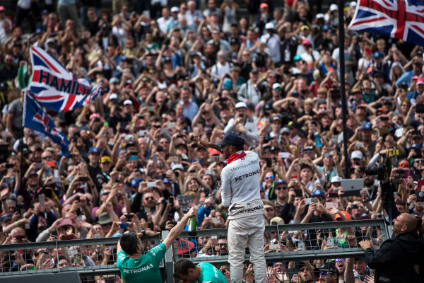 Silverstone, Northamptonshire, UK Sunday 10 July 2016. Lewis Hamilton, Mercedes AMG, 1st Position, celebrates victory at his home race with the fans. World Copyright: Ferraro/LAT Photographic ref: Digital Image _FER9089