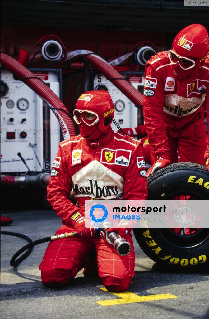 Ferrari mechanics await one of their cars in the pits.