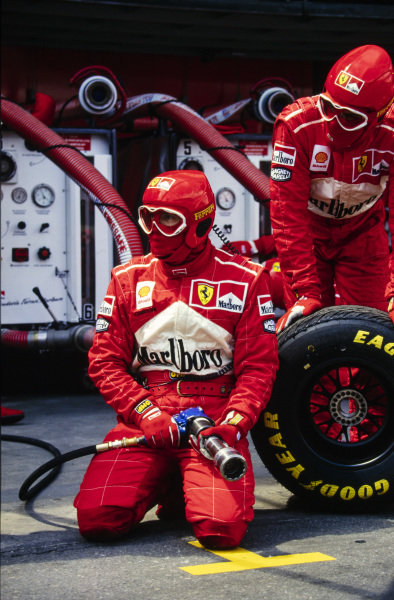 Ferrari mechanics await one of their cars in the pits.