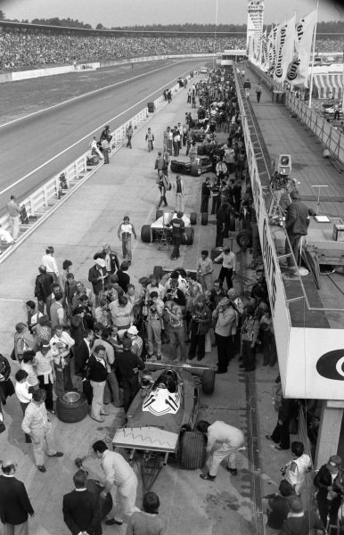 A shot of the pitlane with cars being worked on and photographers taking pictures, especially of Niki Lauda's Ferrari 312T2 (#11).