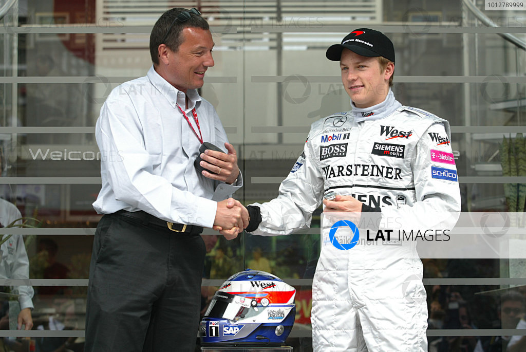2003 Spanish Grand Prix - Sunday Race,Barcelona, Spain.4th May 2003.Kimi Raikkonen, Team McLaren Mercedes MP4/17D, is presented with the new TAG Heuer link watch to commemorate his first Formula One win in the 2003 Malaysian Grand Prix by Jean-Christophe Babin (TAg Heuer CEO).World Copyright LAT Photographic.ref: Digital Image Only.