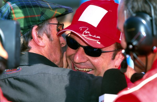 Former F1 world champion Jackie Stewart (GBR), left, congratulates former Stewart Grand Prix driver Rubens Barrichello (BRA), Ferrari, on his unexpected race win.
