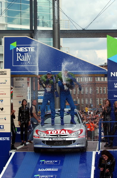 Rally winner Marcus Gronholm (FIN) and team mate Timo Rautiainen (FIN) Peugeot 206 WRC spray champagne. FIA World Rally Championship, Rd9, Neste Rally Finland, Day Three, Finland. 11 August 2002. DIGITAL IMAGE
