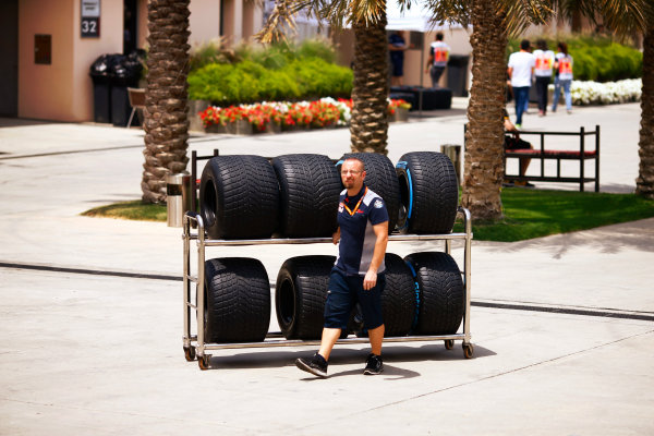Bahrain International Circuit, Sakhir, Bahrain.  Thursday 13 April 2017. A Red Bull mechanic with tyres in the paddock. World Copyright: Andy Hone/LAT Images ref: Digital Image _ONZ6615