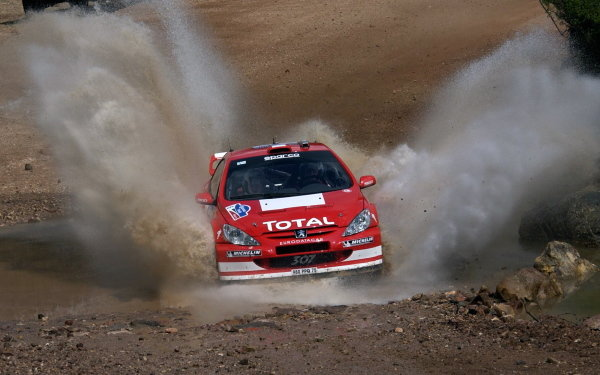 Marcus Gronholm (FIN) / Timo Rautiainen (FIN) Peugeot 307 WRC goes through a watersplash.World Rally Championship, Rd3, Rally Mexico, Leon, Mexico. Day Three. 14 March 2004.DIGITAL IMAGE