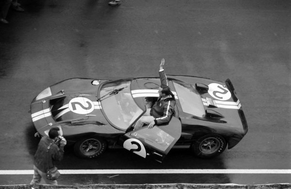Chris Amon waves to the crowd from the cockpit of his Shelby American Inc., Ford Mk II.