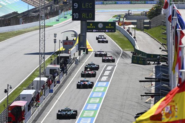 Lance Stroll, Aston Martin AMR21, Antonio Giovinazzi, Alfa Romeo Racing C41, Fernando Alonso, Alpine A521, and Sebastian Vettel, Aston Martin AMR21, leave the pits