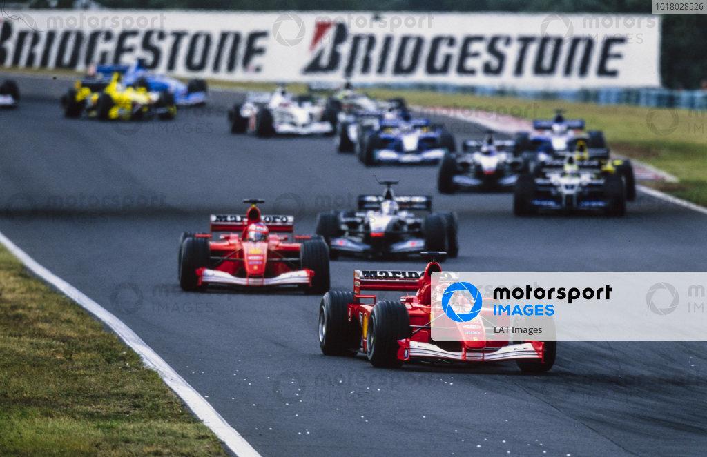 Michael Schumacher, Ferrari F2001, leads Rubens Barrichello, Ferrari F2001, and David Coulthard, McLaren MP4-16 Mercedes, into the second corner at the start.