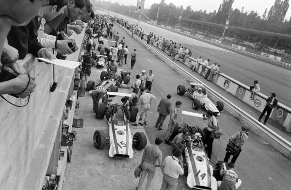 The Honda RA301s of David Hobbs and John Surtees at the end of the pit lane as Jo Bonnier, McLaren M5A BRM, passes by.