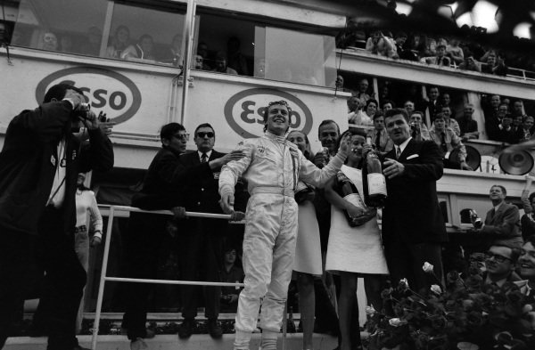 Jackie Oliver celebrates victory on the podium with a magnum of champagne.