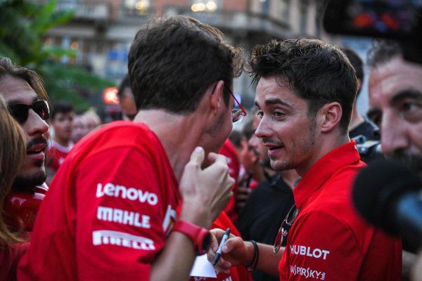 Charles Leclerc, Ferrari talks to a fan as he signs an autograph