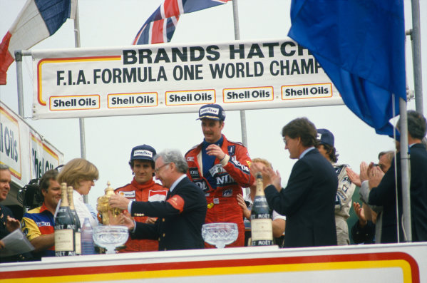 Brands Hatch, England. 11-13 July 1986.  Nigel Mansell (Williams FW11-Honda) 1st position, Nelson Piquet (Williams FW11-Honda) 2nd position and Alain Prost (McLaren MP4/2C-TAG Porsche) 3rd position on the podium, with Mrs Virgina Williams receives the constructors trophy, portrait.  World Copyright: LAT Photographic. Ref:  86GB68