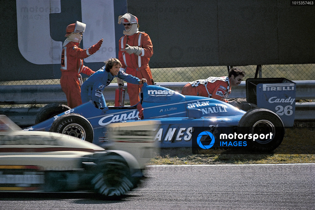 Jacques Laffite helps a marshal to push his Ligier JS25 Renault.