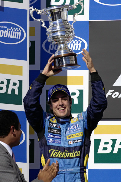 Fernando Alonso raises his 2nd place trophy on the podium.