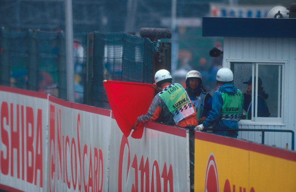 Suzuka, Japan. 4th - 6th November 1994. A marshall hangs out the red flag as the Grand Prix is stopped due to the accidents of Herbert, Inoue and Katayama which blocked the circuit.Ref-94 JAP 05.World Copyright - LAT Photographic