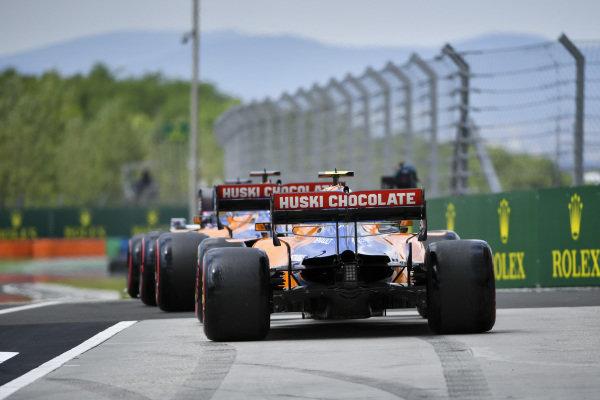 Carlos Sainz Jr., McLaren MCL34, leads Lando Norris, McLaren MCL34, out of the pits