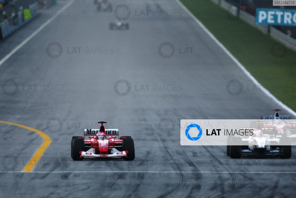 2003 Malaysian Grand Prix. Sepang, Kuala Lumpur, Malaysia.21-23 March 2003.Rubens Barrichello (Ferrari F2002) passes Jenson Button (B.A R. 005 Honda), with Olivier Panis (Toyota TF103) behind.World Copyright - LAT Photographic ref: Digital Image Only