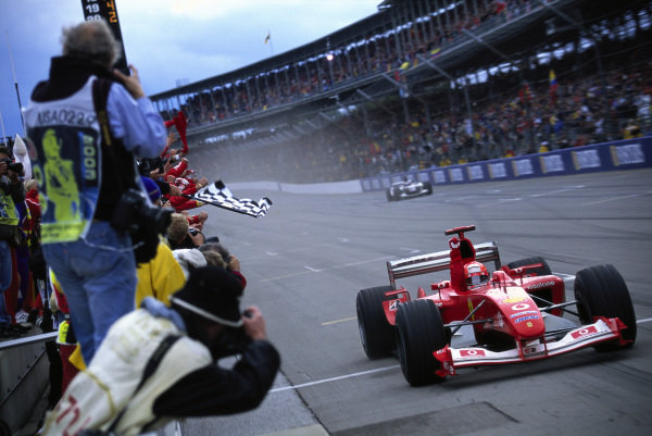 Michael Schumacher, Ferrari F2003-GA, kicks up dust as he crosses the finish line and takes the chequered flag at the end of the race.