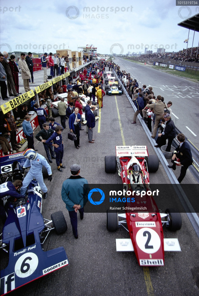 Jacky Ickx, Ferrari 312B2, on his way out of the pits, while Francois Cevert steps into the cockpit of his Tyrrell 002 Ford.