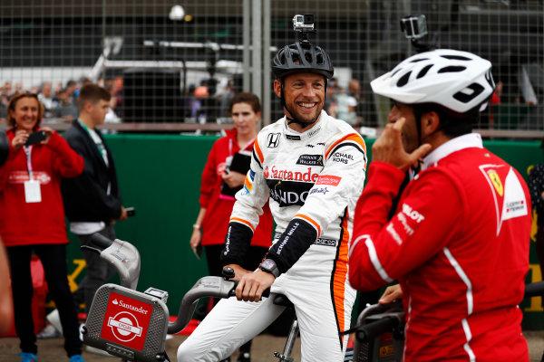 Silverstone, Northamptonshire, UK.  Thursday 13 July 2017. Jenson Button, McLaren, and Marc Gene of Ferrari sit astride bicycles. World Copyright: Glenn Dunbar/LAT Images  ref: Digital Image _31I2287