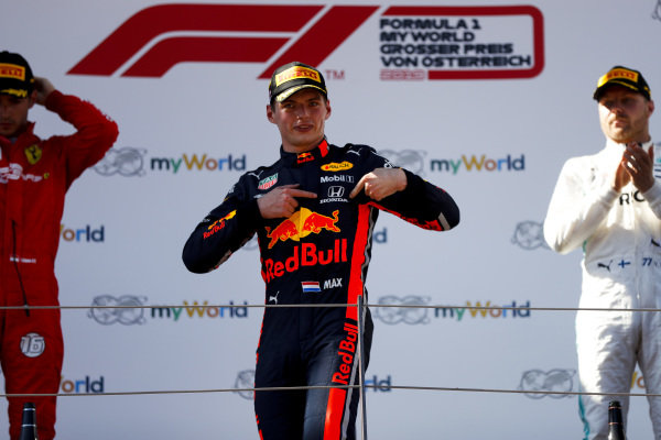 Max Verstappen, Red Bull Racing, 1st position, points to his Honda badge on the podium
