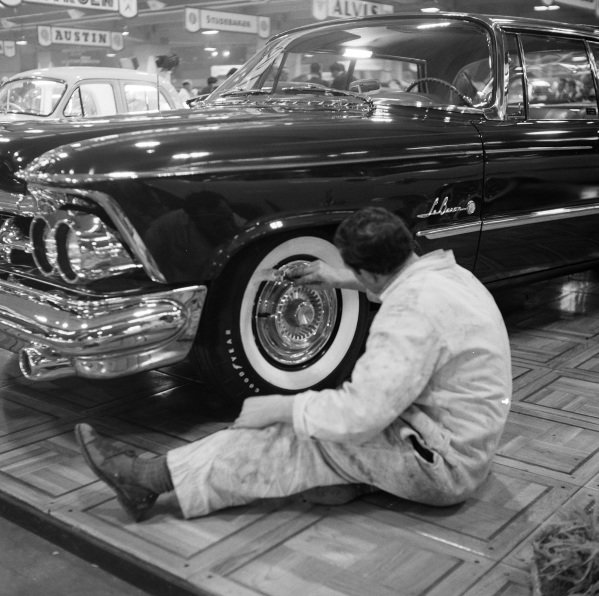 Painting the tyres of a Chrysler Imperial.