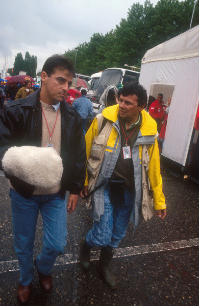 1991 San Marino Grand Prix.Imola, Italy.26-28 April 1991.Alessandro Nannini with photographer, Ercole Colombo in the Imola paddock. The sheepskin glove protects his right hand which was severed in the helicopter crash last September. Ref-91 SM 16.World Copyright - LAT Photographic