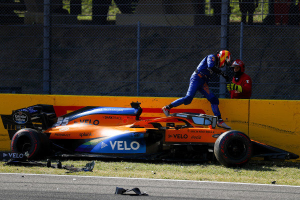 Carlos Sainz, McLaren, climbs out of his damaged car after crashing out