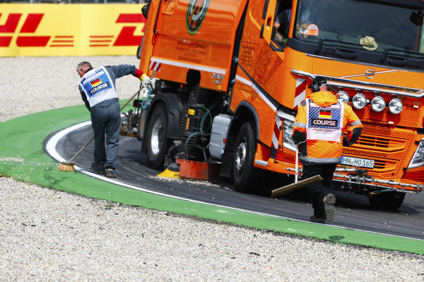 Gravel is cleared from the circuit by marshals after an off-track moment by Marcus Ericsson, Sauber C37 Ferrari.