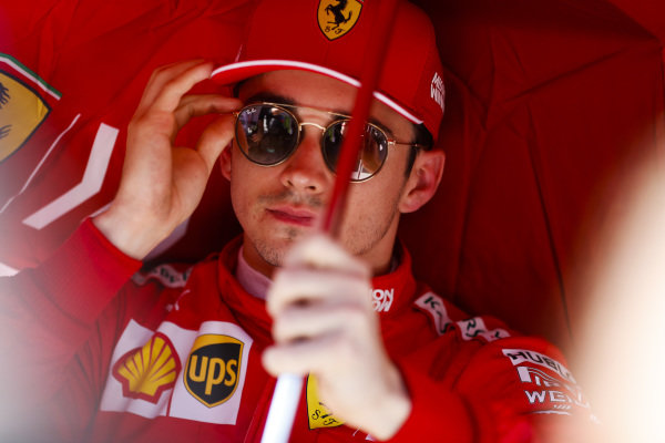 Charles Leclerc, Ferrari SF90, sits under an umbrella on the grid