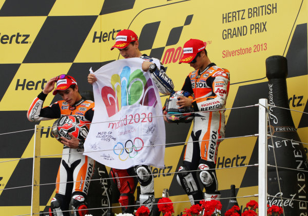 British Grand Prix.  Silverstone, England. 30th August - 1st September 2013.  Jorge Lorenzo, Yamaha, Marc Marquez and Dani Pedrosa, Honda, on the podium with a flag to support Madrid's bid to host the 2020 Olympic games.  Ref: IMG_2560a. World copyright: Kevin Wood/LAT Photographic