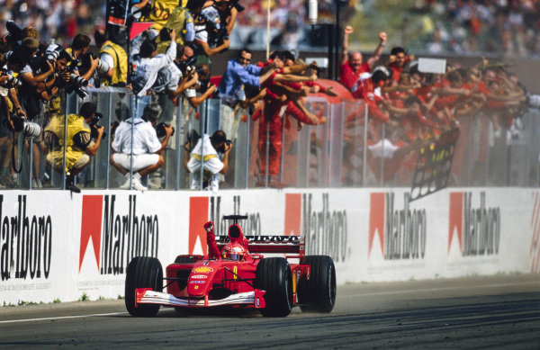 Michael Schumacher, Ferrari F2001, celebrates winning his fourth world drivers' championship with the team as he crosses the finish line.