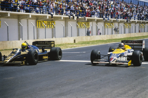 Ayrton Senna, Lotus 98T Renault, leads Nigel Mansell, Williams FW11 Honda, across the line in one of the closest finishes in Formula 1 history.