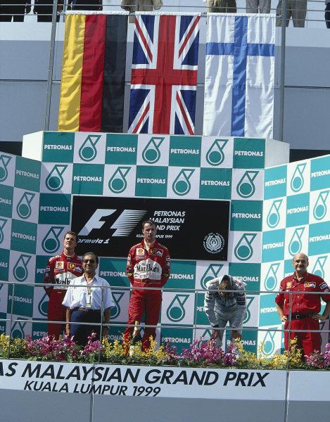 1999 Malaysian Grand Prix.Sepang, Kuala Lumpur, Malaysia. 15-17 October 1999.Eddie Irvine (Ferrari) 1st position, Michael Schumacher (Ferrari) 2nd position and Mika Hakkinen (McLaren Mercedes) 3rd position on the podium.Ref-99 MAL 19.World Copyright - LAT Photographic