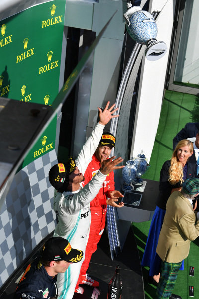 Lewis Hamilton, Mercedes AMG F1, 1st position, tosses his trophy in the air in celebration alongside Max Verstappen, Red Bull Racing, 2nd position, and Sebastian Vettel, Ferrari, 3rd position