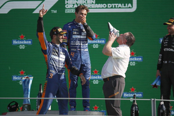Daniel Ricciardo, McLaren, 1st position, and Lando Norris, McLaren, 2nd position, cheer as Zak Brown, CEO, McLaren Racing, performs a shoey on the podium