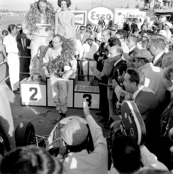 1964 Mexican Grand Prix.Mexico City, Mexico, 25 October 1964.John Surtees (Ferrari 158) celebrates on the podium as he becomes the only man to win World Championships on motorbikes and in a car. Race winner Dan Gurney (Brabham BT7-Climax) looks on as does Stirling Moss and HRH Prince Philip. Ref-27505 40mb Scan from B&W PrintWorld Copyright: LAT Photographic